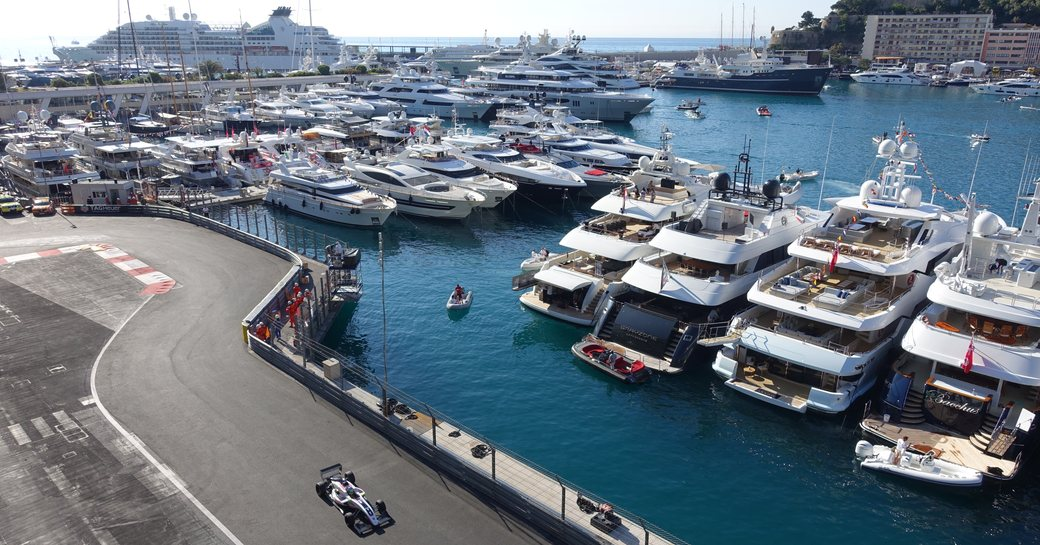 Charter yachts lining up next to racing circuit as car speeds around the track at Formula 1 Monaco Grand Prix