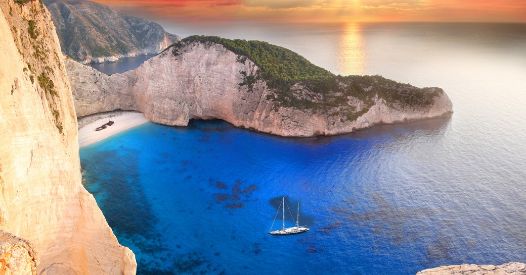 sailing yacht anchors in waters off Navagio beach as the sun sets