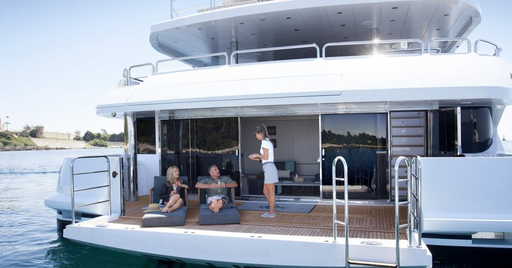 guests lounge on sunpads while crew member serves drinks on the beach club of superyacht ARADOS