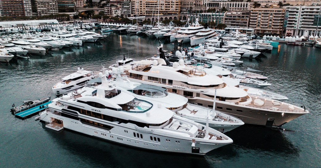 Superyachts moored along jetty at Monaco Yacht Show, Monte Carlo in background.