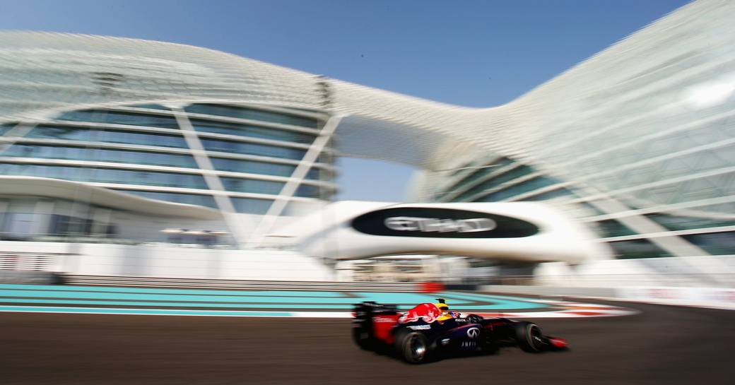 Car in focus as it goes under Etihad signage with arches of Yas Viceroy Hotel above during Abu Dhabi Grand Prix