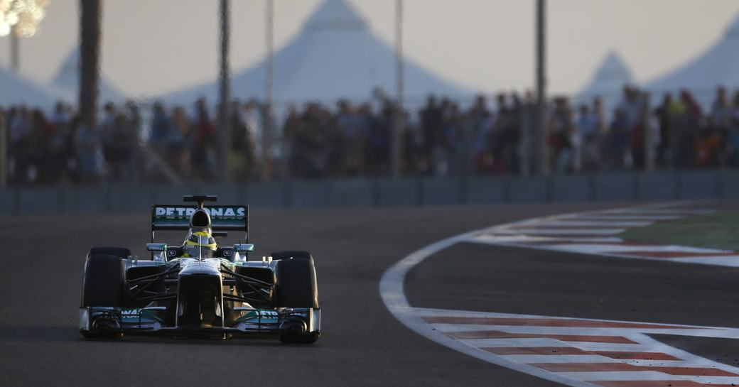 Racer in action on Abu Dhabi Grand Prix track, dusk falling with floodlights on in background.