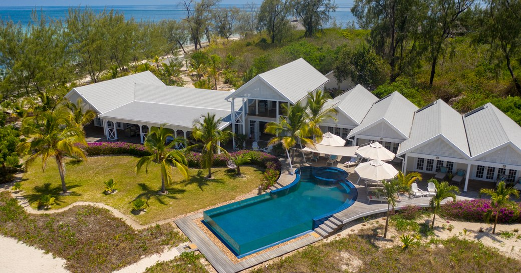 aerial shot of the villa on thanda island, with infinity pool and palm trees, as well as sandy strip of beach visible