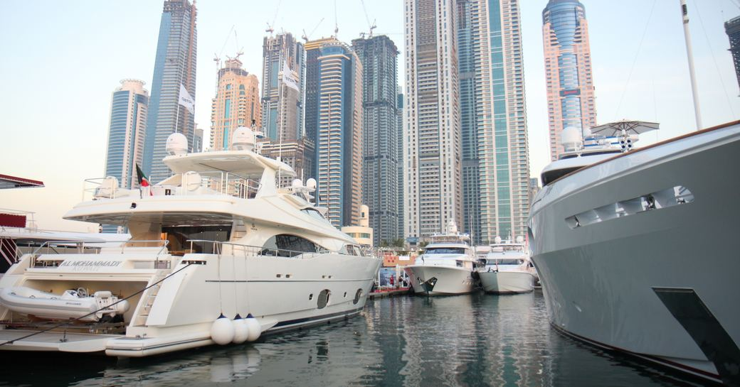 Luxury yachts in marina in Dubai with skyscrapers in background