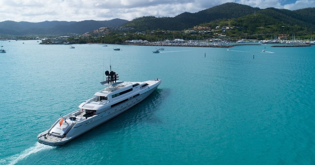 Superyacht cruises up to Coral Sea Marina Resort ahead of Australian Superyacht Rendezvous, with blue sea and green landscapes in background