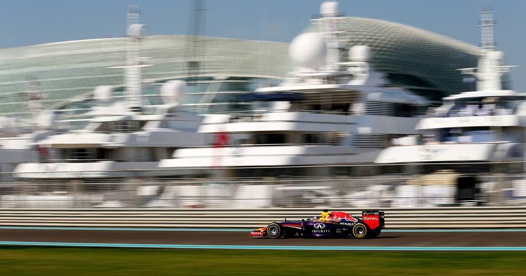 Car on racetrack going past superyachts at Yas Marina Racing Circuit