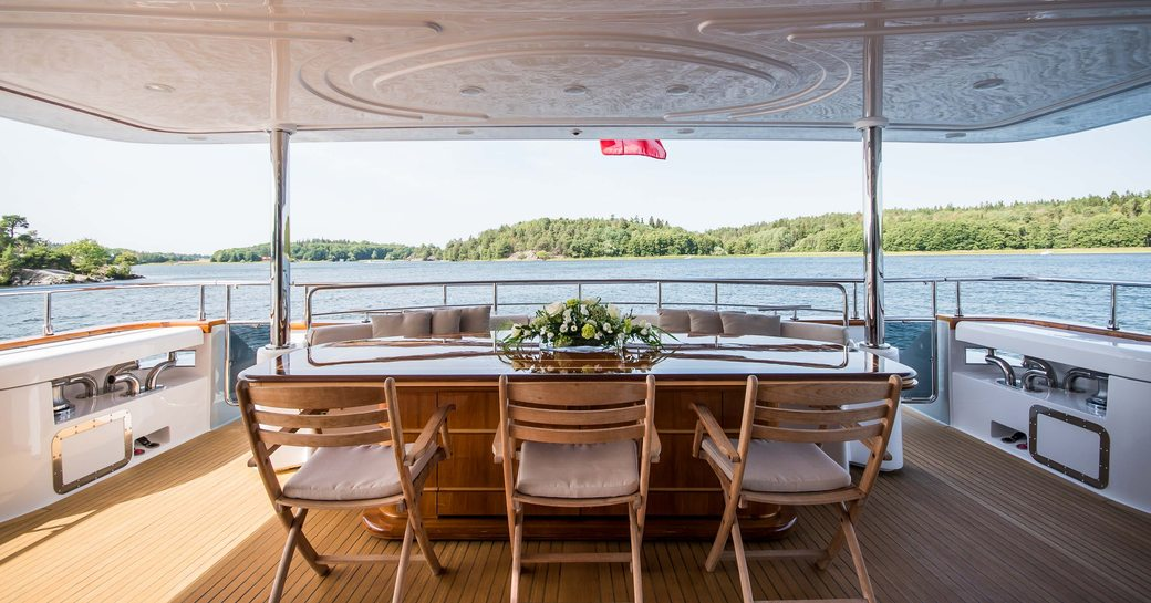 Covered dining area on deck of Superyacht Queen of Sheba with forested coast in background