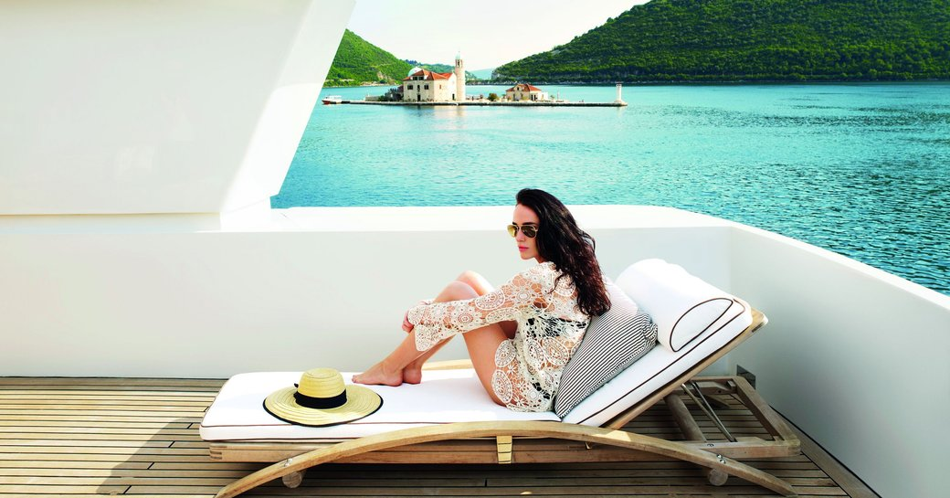 charter guest relaxes on a lounger while cruising in Montenegro