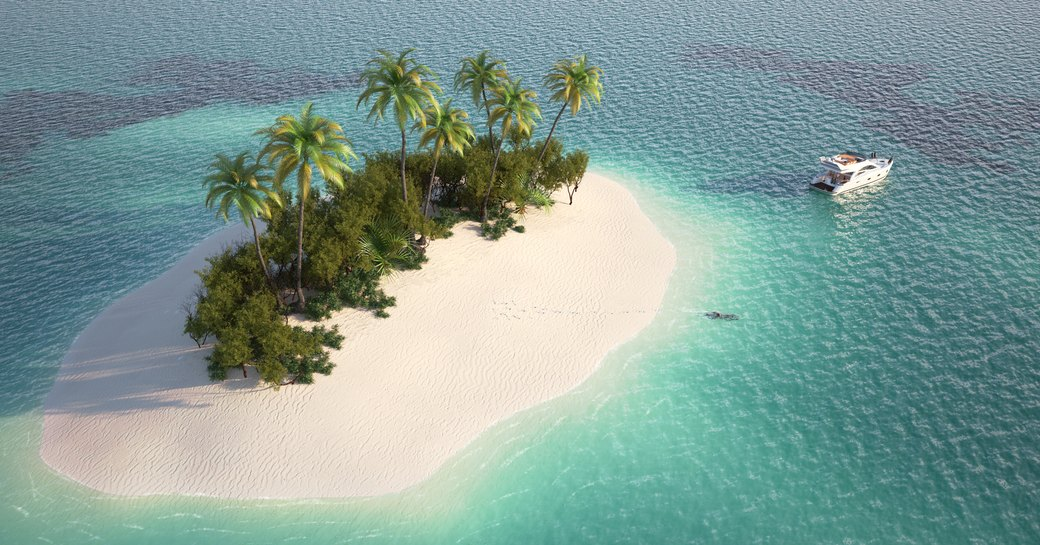 Remote Caribbean island with palms surrounded by clear teal waters and a yacht anchored by the shore