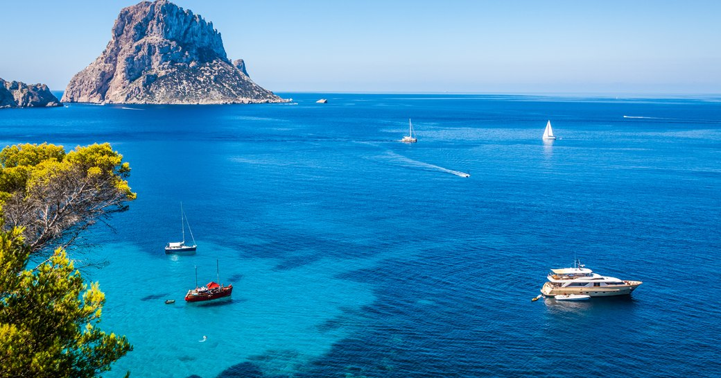 Yachts in Cala d'Hort, Ibiza. Clear blue water and rugged mountain in background