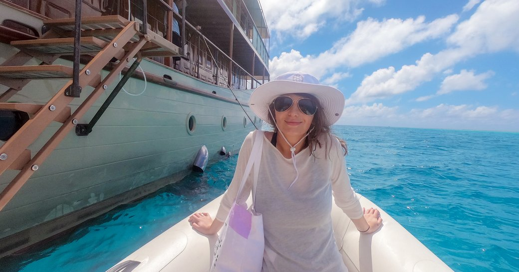 woman sits on tender next to luxury charter yacht over the rainbow in east africa