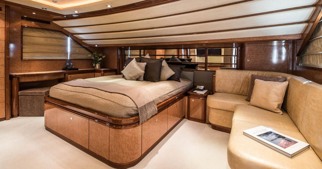 Elegant mastersuite on Superyacht Queen of Sheba with bed and leather sofa visible