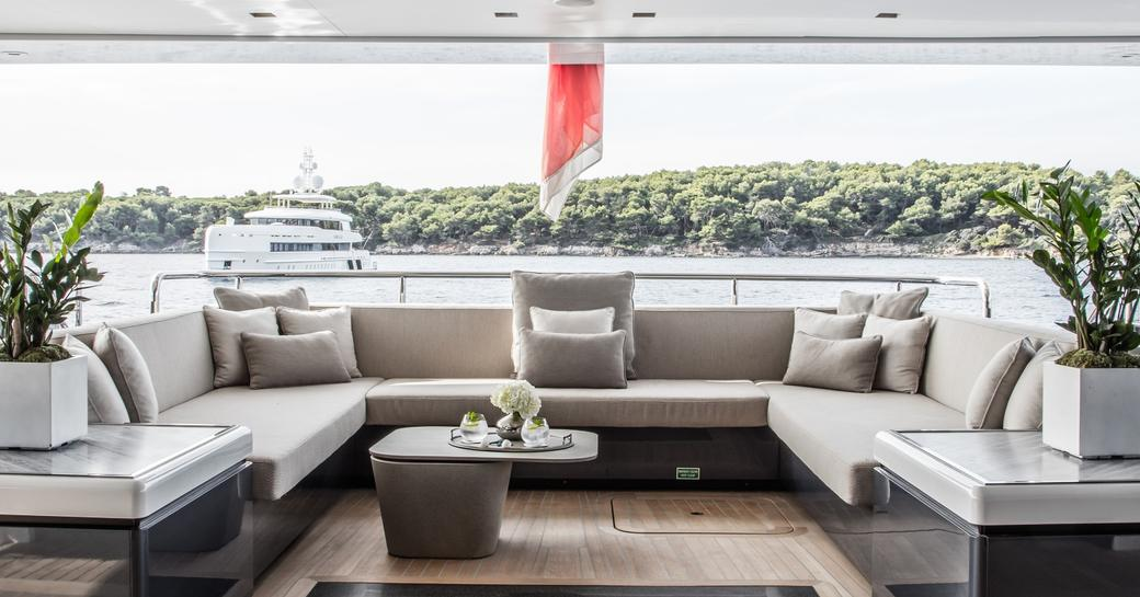 Large comfortable seating area on outside deck of superyacht SEVERIN'S with coastline and another yacht in background