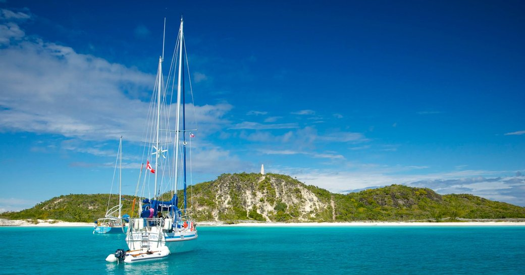 A sailing yacht approaches an island in the Bahamas