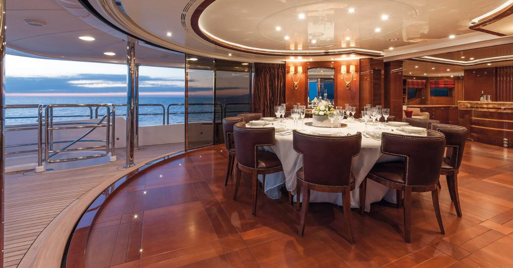 indoor-outdoor dining area on the upper deck aft of superyacht CHECKMATE