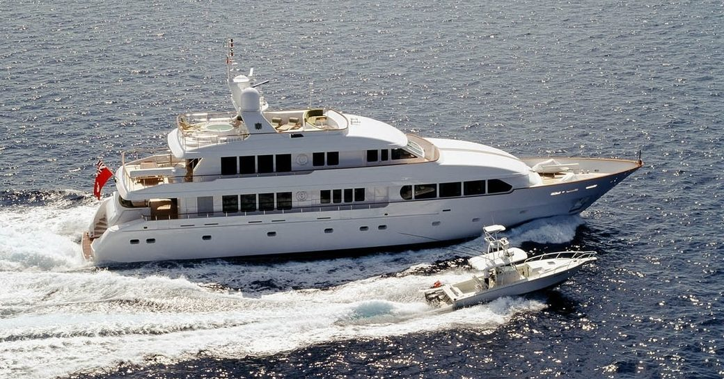 superyacht M4 cutting through the water with her tender on a Bahamas yacht charter