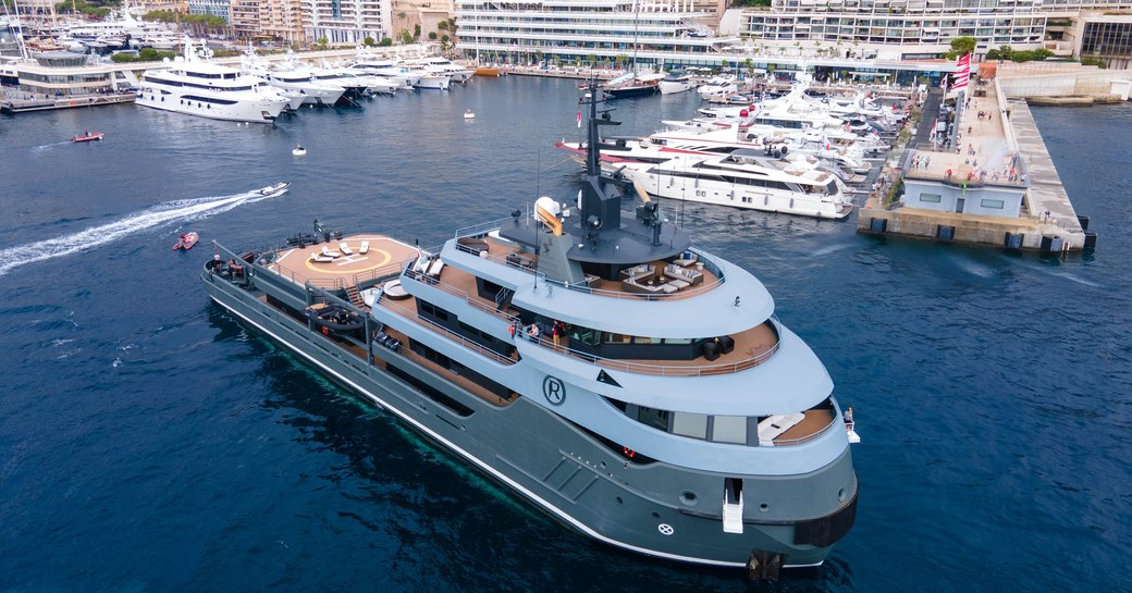Explorer yacht RAGNAR arriving at Yacht Club de Monaco in  busy port with town in background