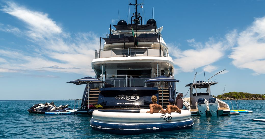 The aft section of superyacht 'Take 5' with two guests on an inflatable
