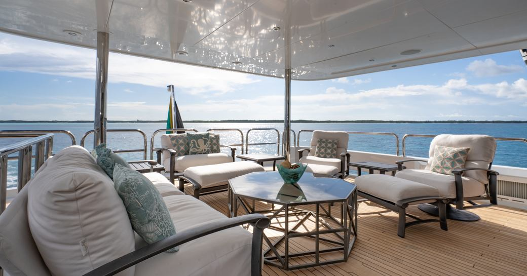 Covered area on deck of superyacht ZEAL with comfortable seats