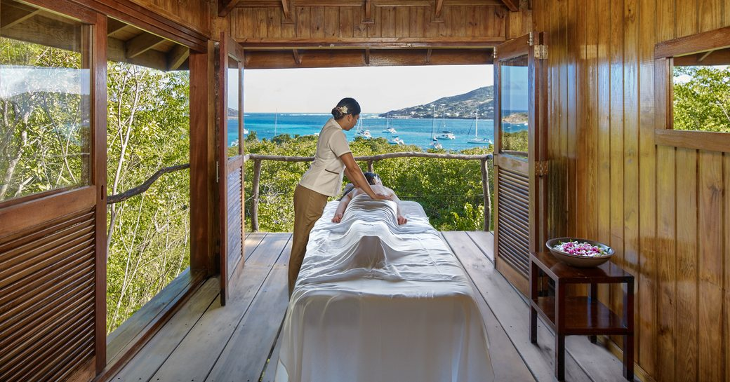 A woman receives a massage on a bed looking out across the Caribbean beach