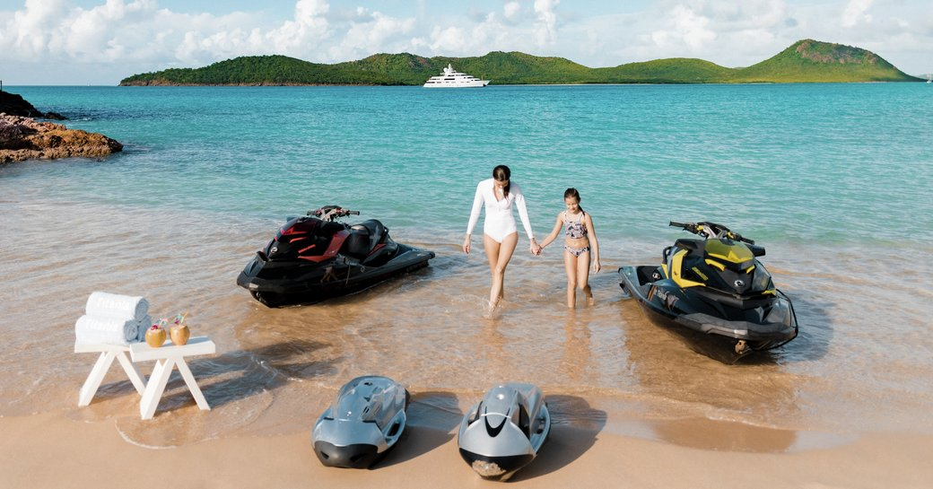 A couple with jet skis ashore with view of MY Titania