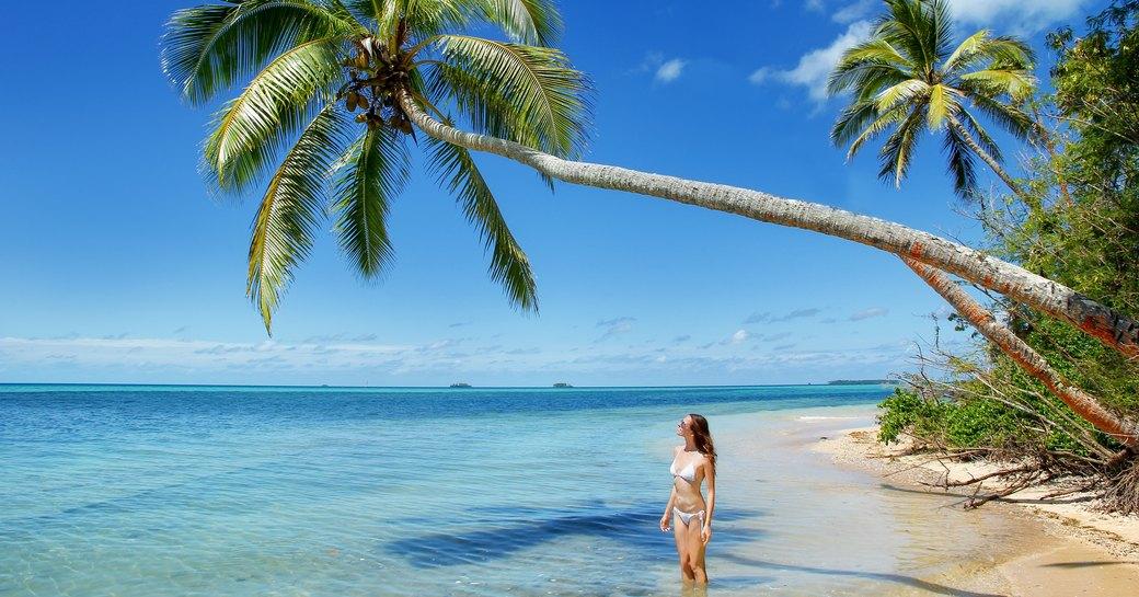 woman stands under a leaning palm tree on beach on Makaha'a island near Tongatapu island in Tonga