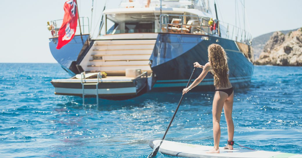 charter guest goes paddle boarding with superyacht Q anchored nearby