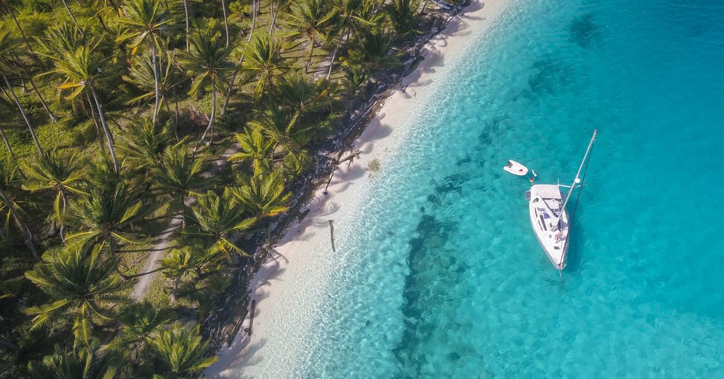 white Sailing Yacht anchored in crystal clear Turquoise Water right next to the perfect White Sand Beach of a Tropical Island in the Caribbean