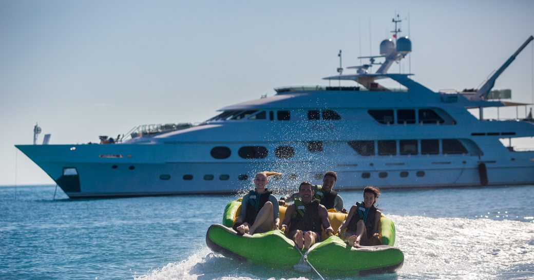 charter guests get out on the towable toys with superyacht Lady Joy in the background