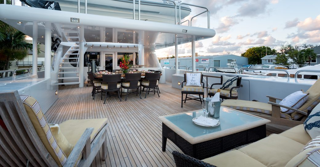 alfresco dining area and sun loungers on the upper deck aft of superyacht STARSHIP