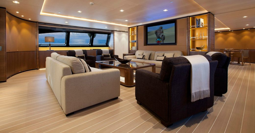 deep sofas and armchairs form a sociable seating area in the main salon of superyacht FIDELIS