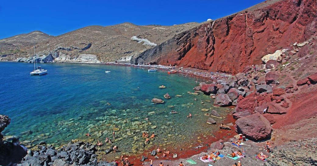 Striking red beach of Santorini with red sand and cliffs