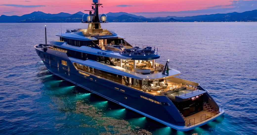 Superyacht SOLO at anchor at night, with green underwater lights and pink sky in background