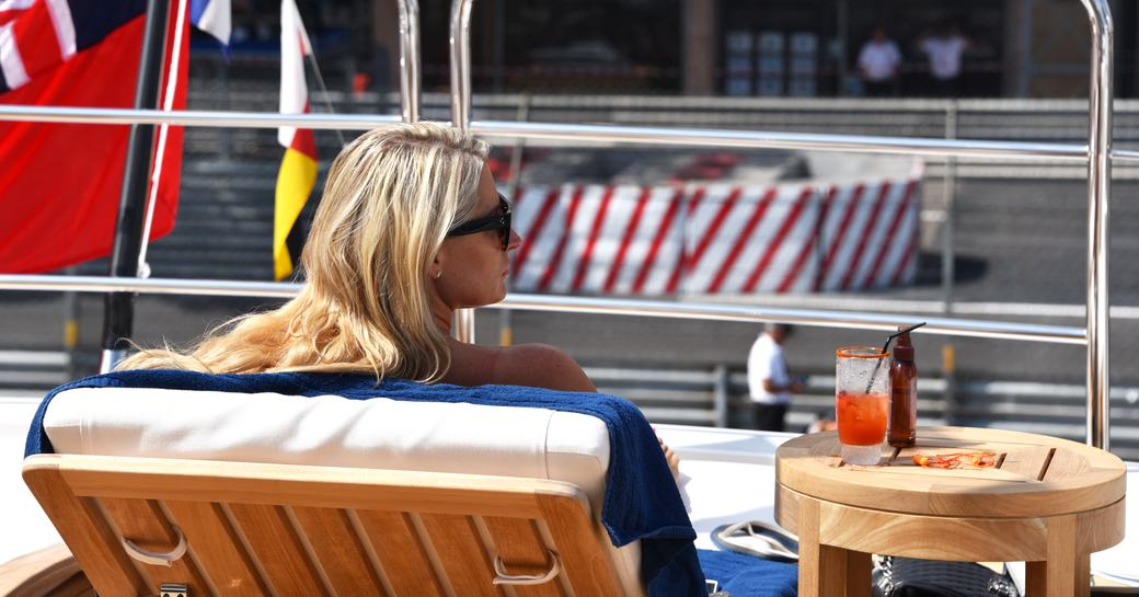 spectator on a sun lounger watches the Monaco Grand Prix from the sundeck of a superyacht berthed in Port Hercules