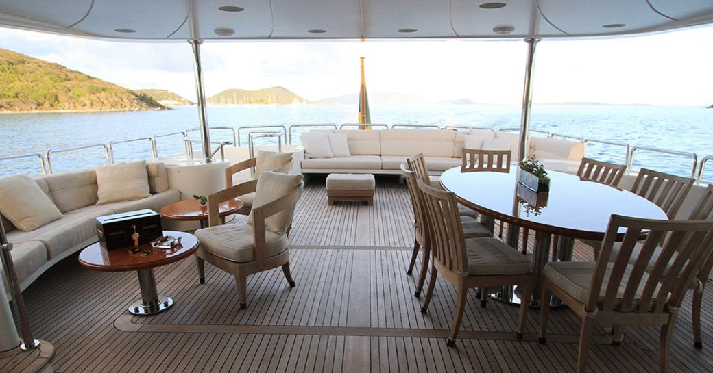 al fresco dining table and seating areas on the upper deck aft of superyacht BRUNELLO