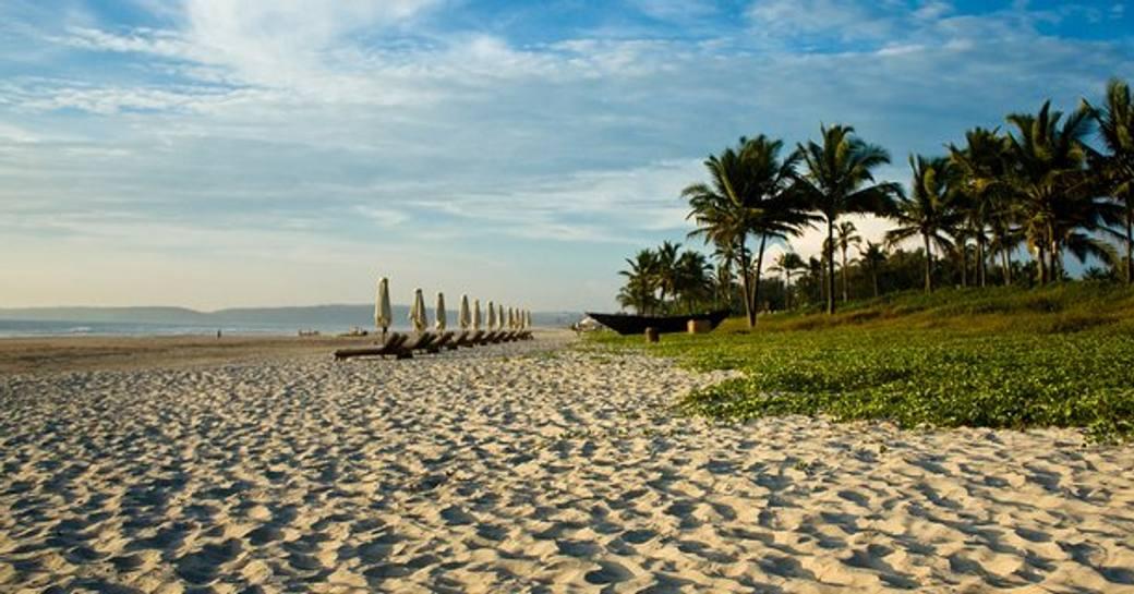 sandy shore and sun loungers lined idyllic side beach along Turkey's Turquoise Coast