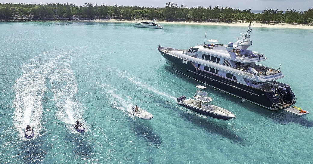 Superyacht M3, with tender and water toys on clear water beside it