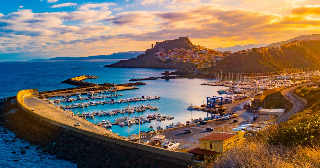 Harbour at sunset in West Mediterranean with rugged hills in background and lots of yachts anchored