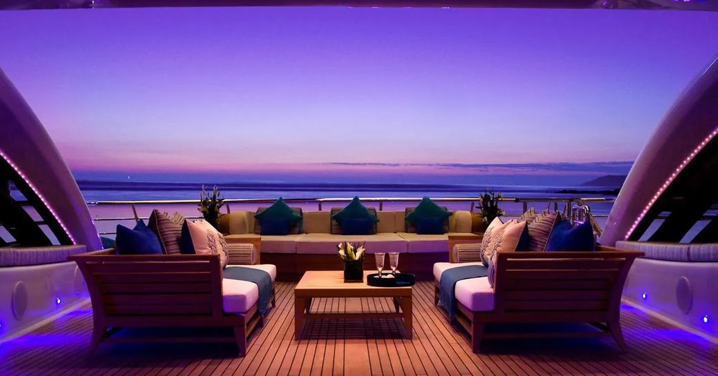 Comfortable seating and table on deck of superyacht Sea Rhapsody