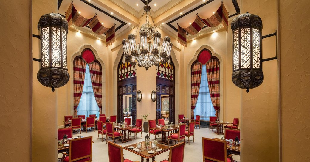 smart red chairs at angular tables in Mezlai Emirati Restaurant in Abu Dhabi