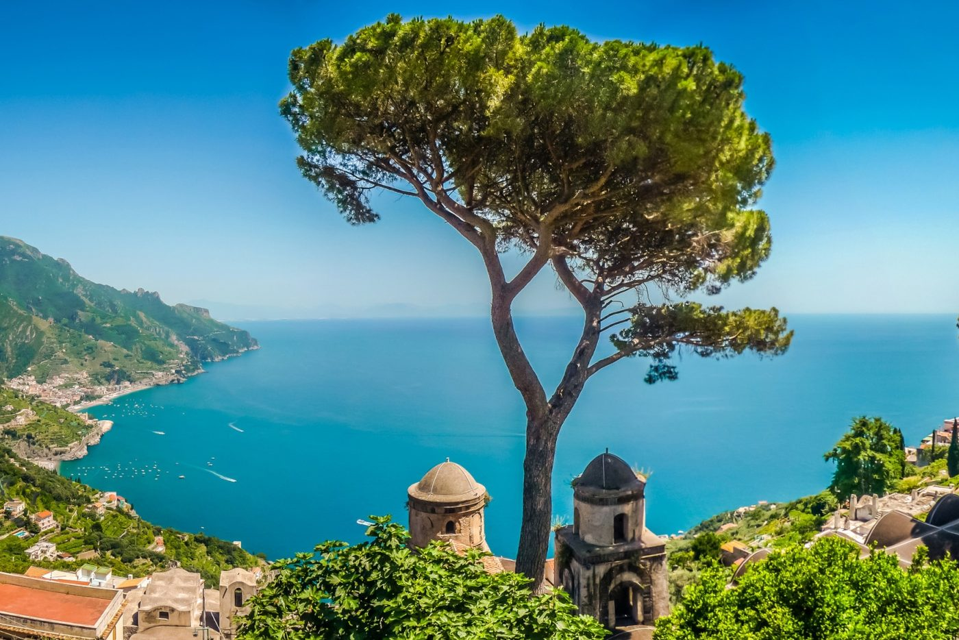 aerial shot of a secluded beach on the amalfi coast from the top of encompassing mountain