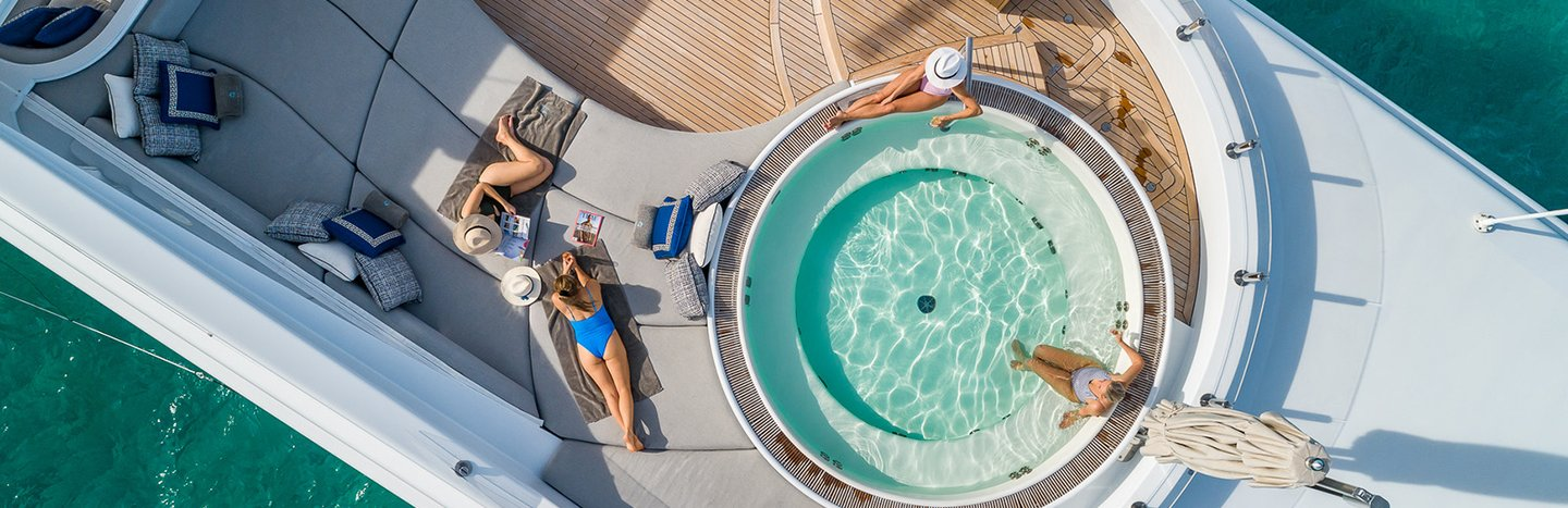 Charter guests relaxing on superyacht sundeck next to Jacuzzi as luxury social distancing vacation