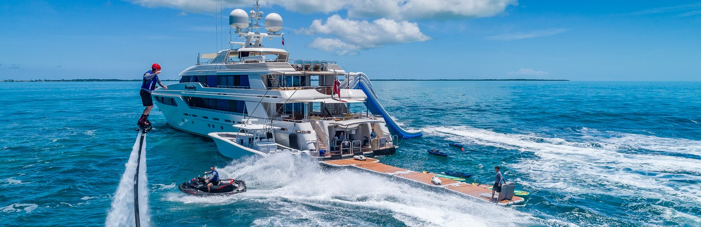 Charter guests enjoying superyacht watertoys as part of social distancing vacation on the water