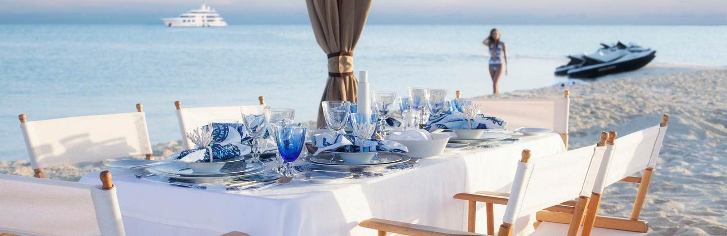 Dining setup on beach for charter guests with superyacht in horizon