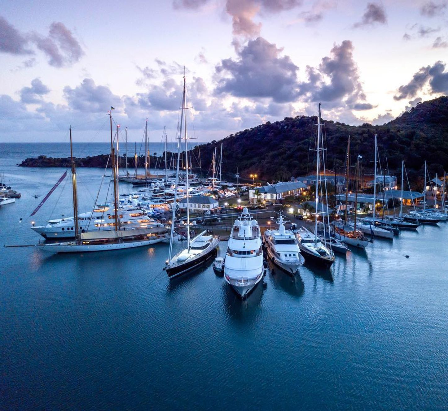 A collection of sailing yachts and motor yachts assembled at sunset for the Antigua Charter Yacht Show 2017