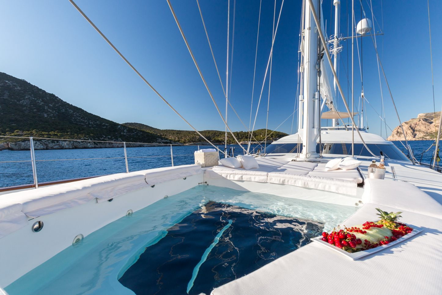 spa pool surrounded by sunpads on the foredeck of sailing yacht Q with platter of fruit