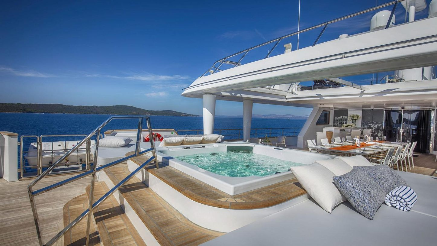 Jacuzzi with alfresco dining area and bar in the background on the sundeck of charter yacht KATINA