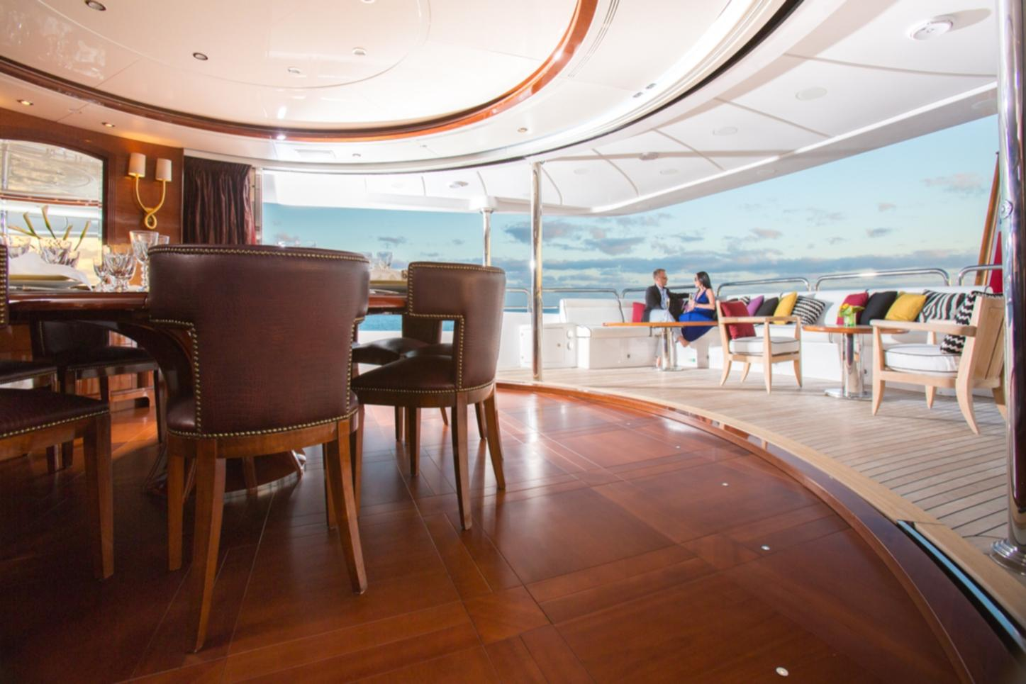 Two charter guests sitting and in conversation on the exterior section of a superyacht