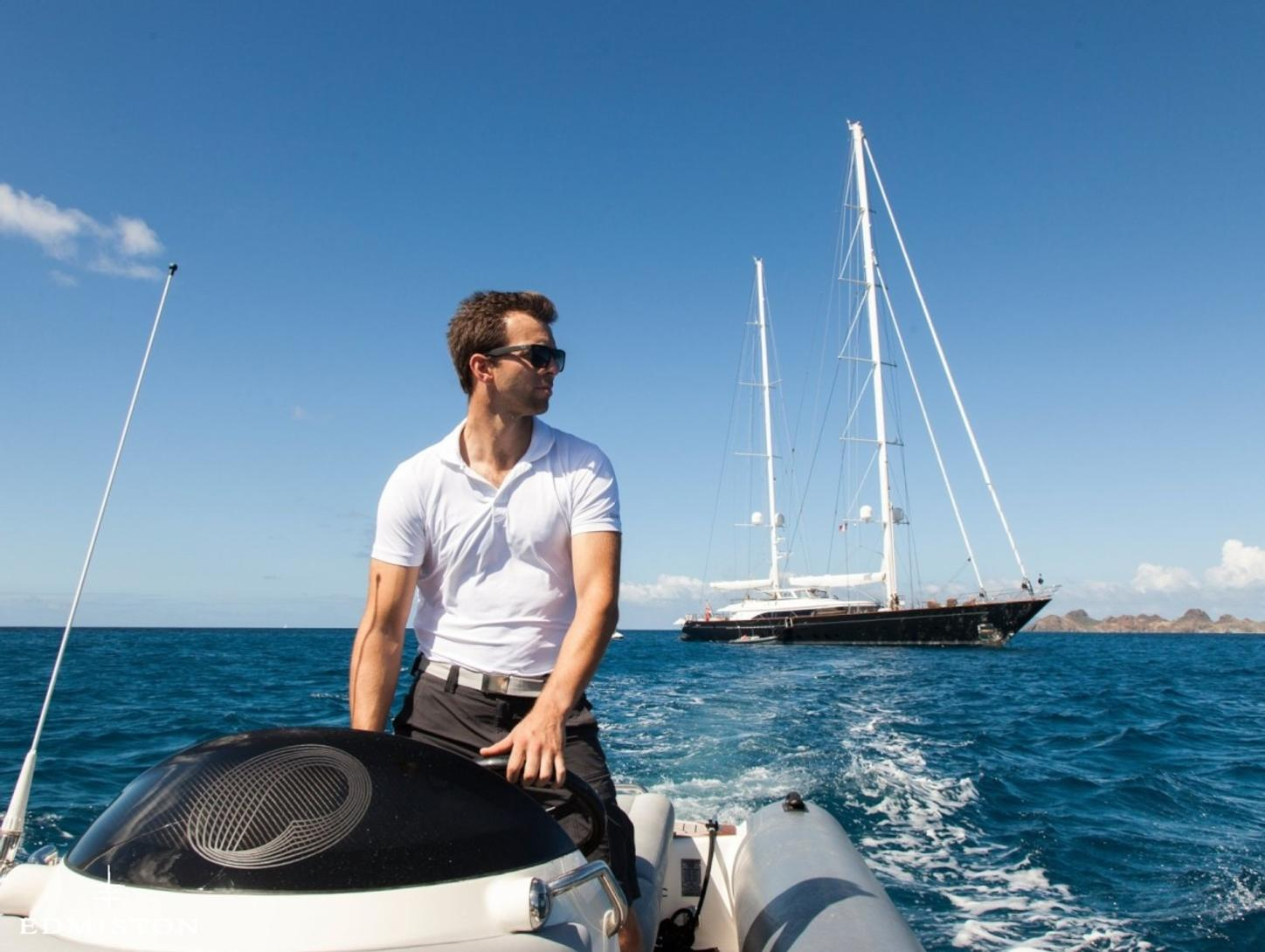 crew member drives a tender as sailing yacht PANTHALASSA anchors in the background while on a Caribbean yacht charter