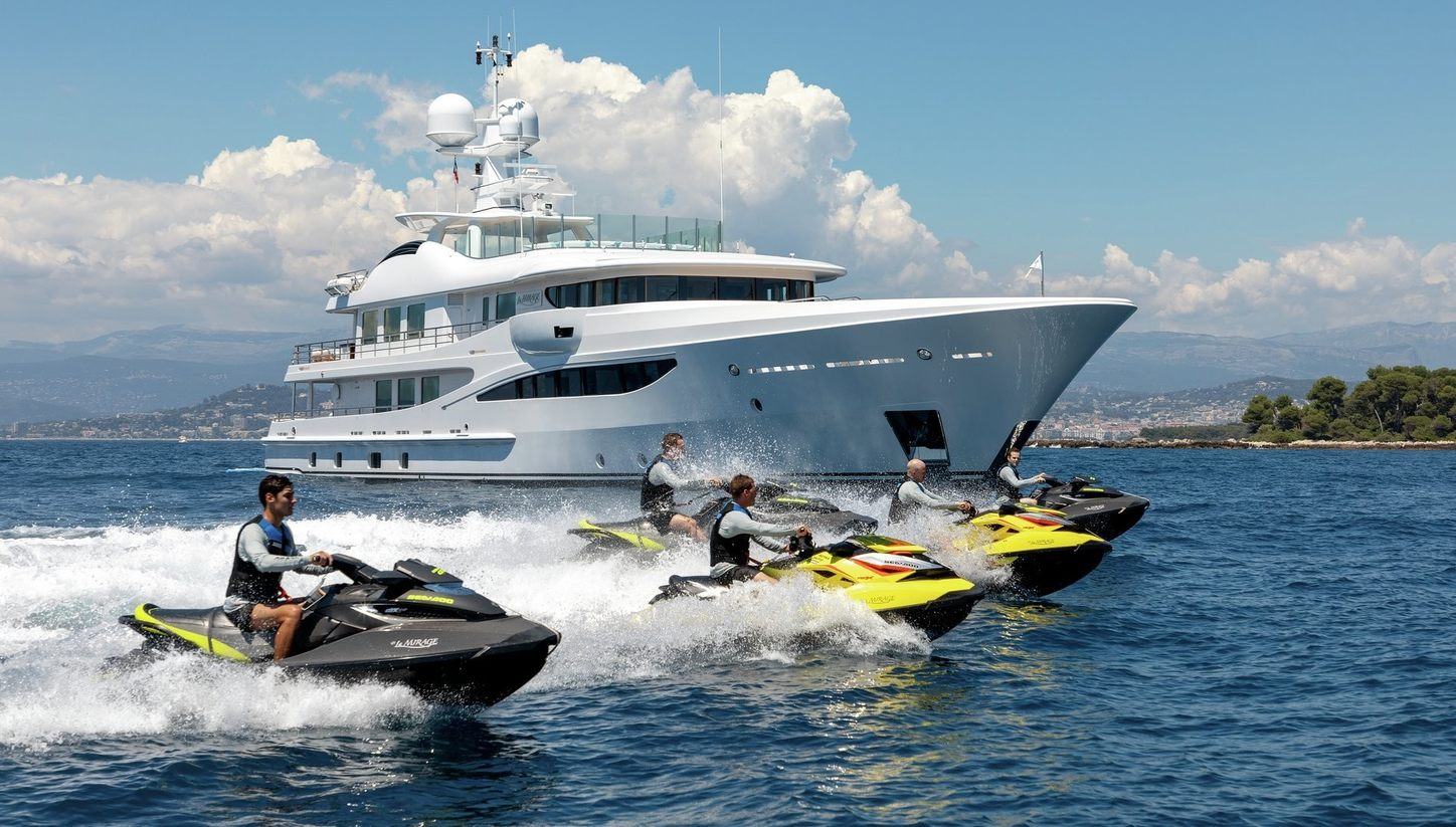 luxury yacht La Mirage cruises on a Mediterranean yacht charter alongside jet skis